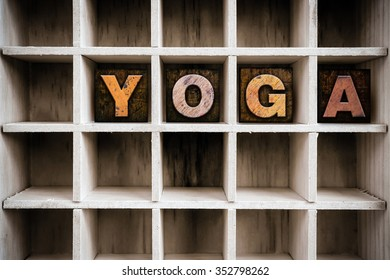 """The word """"YOGA"""" written in vintage ink stained wooden letterpress type in a partitioned printer's drawer."""