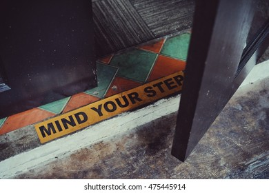 """Wording """"Mind Your Step"""" sticker label or banner put on the floor,Yellow caution sign is label for warning people be careful accident,Business planing concept,color filter effect."""
