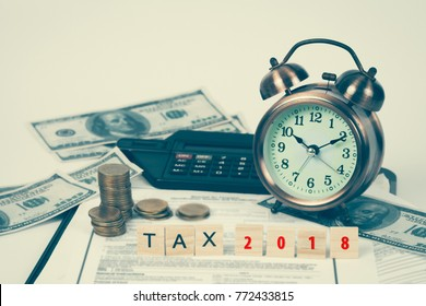 wording tax and calculator with tax documents, money and alarm clock on table. Tax concept.
