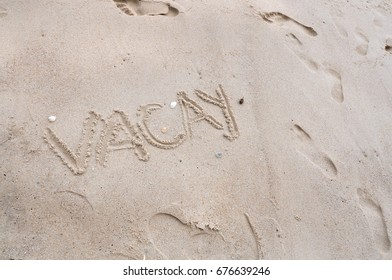 Wording vacay on beach sand with footprint on background
