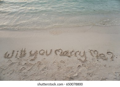 "wording ""Will you marry me?"" write on sand"