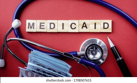 Wording of wooden MEDICAID surround by blue stethoscope against red background. Medical concept.