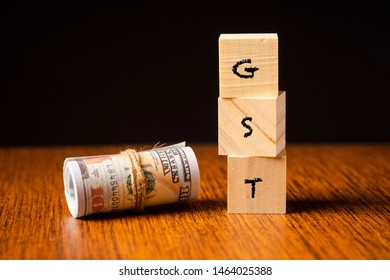 """""""GST"""" wordings on woodens blocks with rolled up money bills. Taxation concept. GST means goods and services tax"""