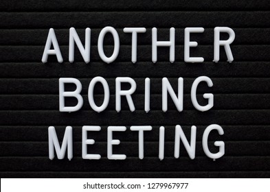 The words Another Boring Meeting in white plastic letters on a black letter board as a reminder to business