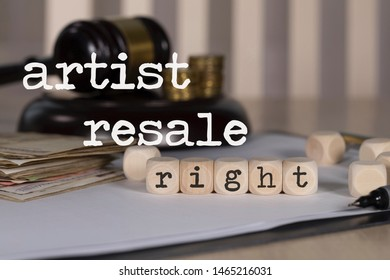Words ARTIST RESALE RIGHTS composed of wooden dices. Auction gavel on the table in the background. Closeup