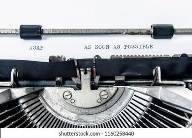 The words ASAP As soon as possible, on a white paper sheet inside an old vintage typewriter.