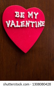 the words be my valentine in glitter letters on a red heart stuck on a wooden cabinet