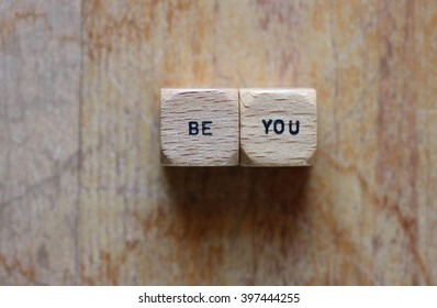 The words Be you printed on two wood dice against wood grain open background for copy