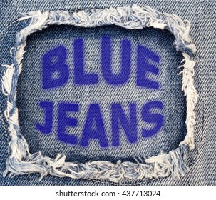 Words Blue Jeans on destroyed torn denim blue jeans patch background, close up
