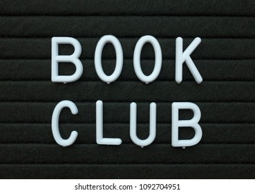 The words Book Club in white plastic letters on a black letter board as a reminder of an event for avid readers and book worms
