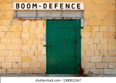 The words Boom Defence are displayed above a sturdy doorway in a stone wall, part of a harbour on the coast of the European island of Malta.