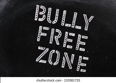 The words Bully Free Zone in chalk stencil letters on a well used blackboard, which might be used for a campaign to stop bullying at school or work
