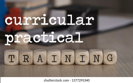 Words CURRICULAR PRACTICAL TRAINING composed of wooden dices. Black graduate hat and books in the background. Closeup