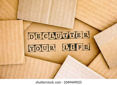 Words Declutter Your Life make by black alphabet stamps on cardboard with some piece of cardboard.
