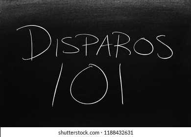 The words Disparos 101 on a blackboard in chalk.  Translation: Shooting 101