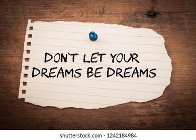 The words don't let your dreams be dreams in paper and old wood