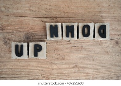 Words up and down wrote in raw cardboard alphabet stamp in wood background. Rustic alphabet stamp with black letters upside down.