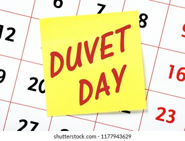 The words Duvet Day on a yellow sticky note with a calendar behind as a reminder to take leave from work