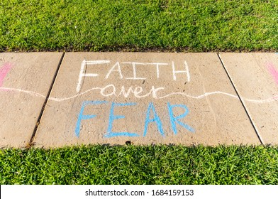 "The words ""Faith over Fear"" written with sidewalk chalk on gray concrete pavement background."