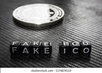 Words fake ico of black cubes and silver coin dark background.