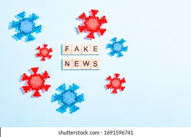Words fake news made of wooden blocks with coronavirus model on blue background, flat lay, top view. Fake news about pandemic concept, disinformation in social media theme