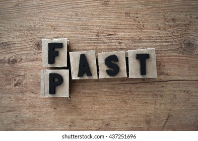 Words fast and past wrote in raw cardboard alphabet stamp in wood background. Rustic alphabet stamp with black letters.