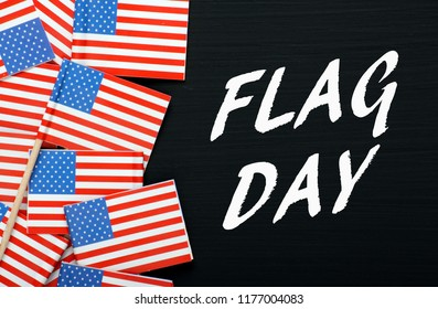 The words Flag Day on a blackboard next to miniature flags of the United States of America