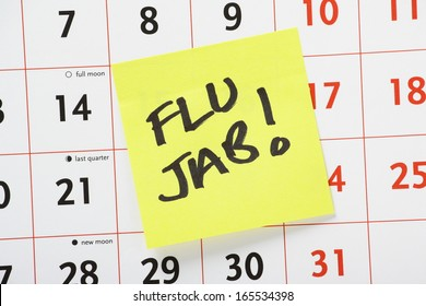 The words Flu Jab written on a yellow sticky paper note and stuck to a wall calendar background as a reminder.