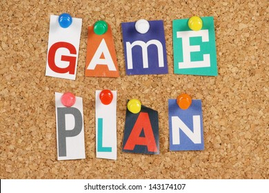 The words Game Plan in cut out magazine letters pinned to a cork notice board.