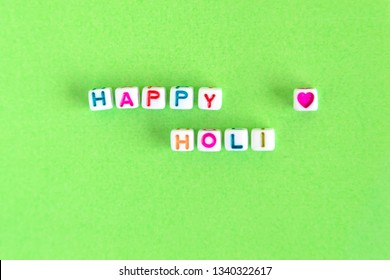 """Words """"Happy Holi"""" made out of beads"""