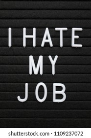 The words I Hate My Job in white plastic letters on a black letter board