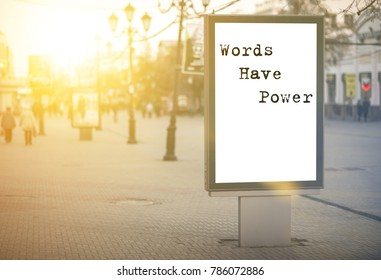 words have power - words, phrase. on a white background billboard in the center of the city against sun rays