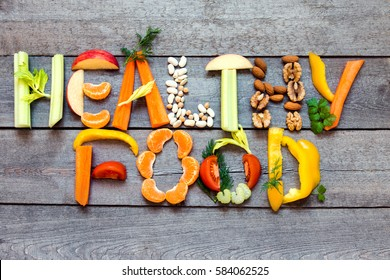 "Words ""Healthy Food"" written with vegetables, fruits, nuts and legumes on rustic wooden background, concept - organic ingredients for healthy vegan diet raw detox food and lifestyle"