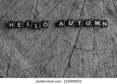 "The words ""hello autumn"" on a wooden background"