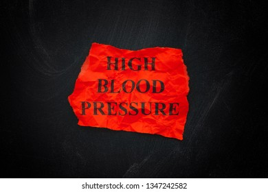 Words High Blood Pressure on red torn piece of paper. Close up.