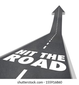 The words Hit the Road on a black pavement street or freeway to illustrate leaving or going on a trip, holiday, vacation, travel or transportation
