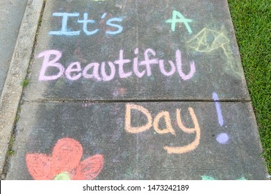 "the words ""It's a Beautiful Day"" written with sidewalk chalk on gray concrete pavement background"