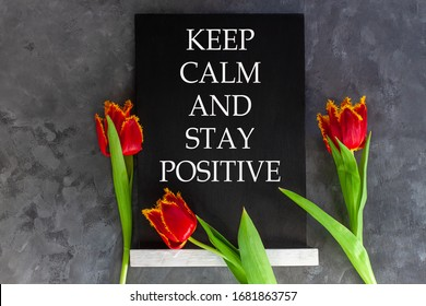 Words Keep Calm And Stay Positive on chalkboard on grey concrete background with fresh tulips. Virus quarantine banner against COVID-19 coronavirus.Blooming flowers flat lay card.Text sign black board