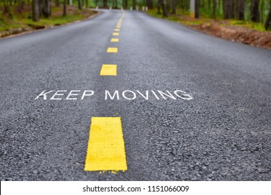 Words of keep moving with yellow line marking on road surface, transportation concept and business idea
