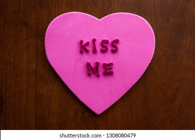 the words kiss me in glitter letters on a pink heart stuck on a wooden cabinet