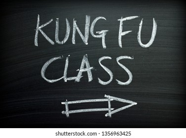 The words Kung Fu Class written by hand in white chalk on a blackboard sign