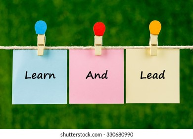 Words of Learn And Lead on sticky color papers hanging by a rope against blurred green background.