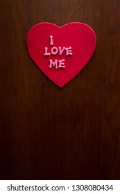 the words I love me in glitter letters on a red heart stuck on a wooden cabinet