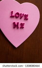 the words love me in glitter letters on a pink heart stuck on a wooden cabinet