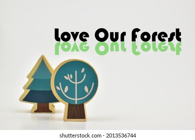 The words Love Our Forest and a block of wood in the shape of two trees