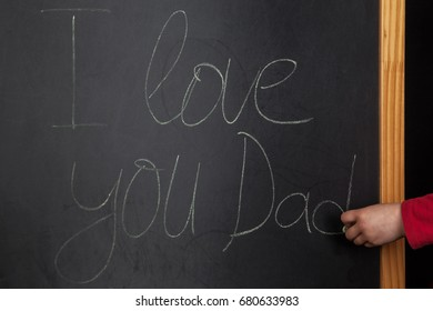 Words I love you Dad writeen on blackboard with child hand holding chalk