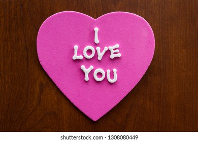the words I love you in glitter letters on a pink heart stuck on a wooden cabinet