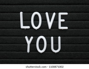 The words Love You in white plastic letters on a black letter board as a romantic message to someone special