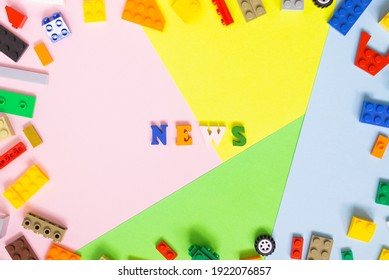 """Words made of multi-colored wooden letters """"news"""" on a multi-colored background, children's construction kit around. Top view."""