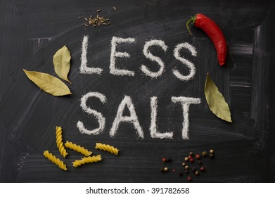Words made of salt describe LESS SALT, decorated with herbs, spices, pasta and red chili